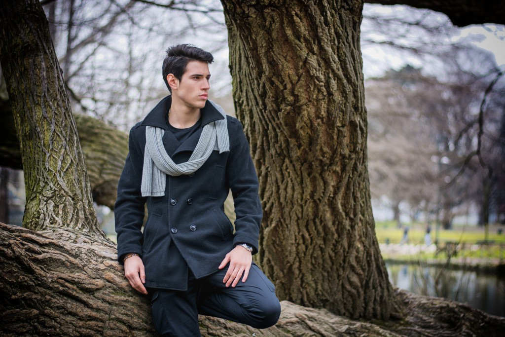 Handsome Stylish Young Man in Black Fashionable Black Winter Coat with Scarf Leaning on Tree Trunk While Looking to the Right of the Frame Seriously.
