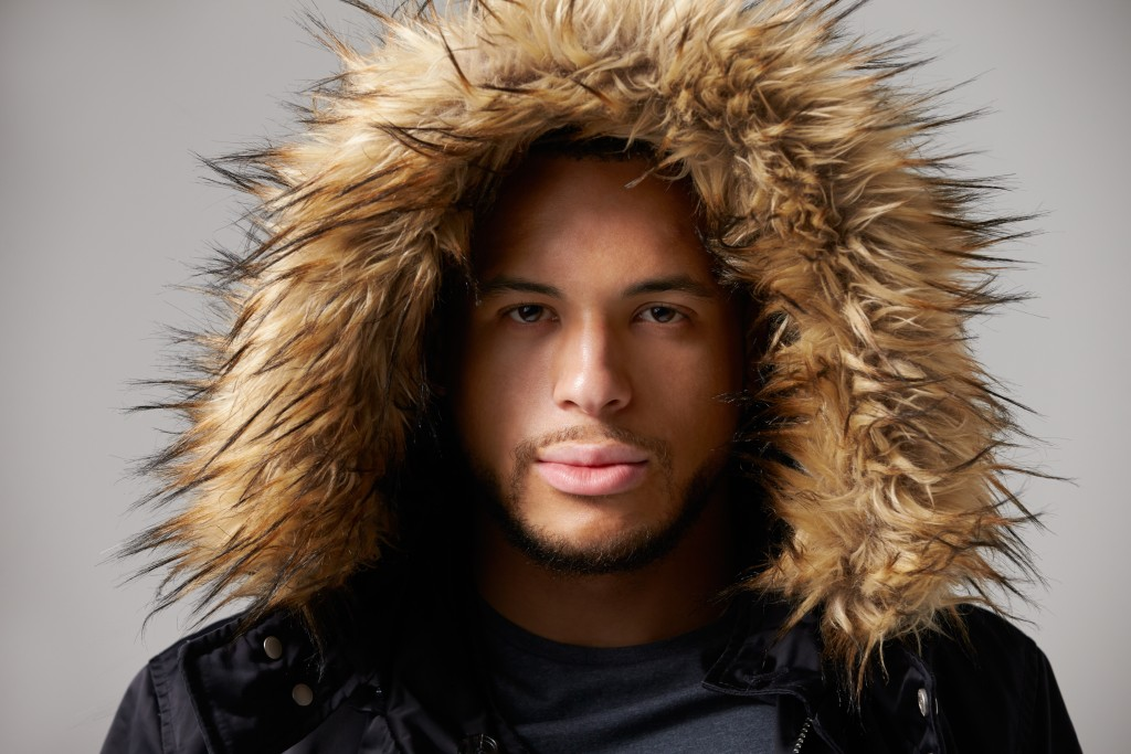 Studio Portrait Of Young Man Wearing Winter Coat